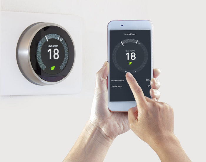 Smart Thermostat with a person saving energy with a smart device on a white background