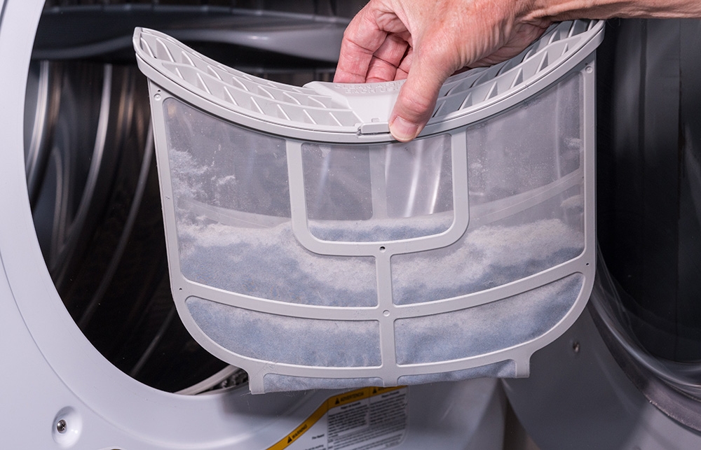 Man holding the lint filled trap from a front loading tumble dryer