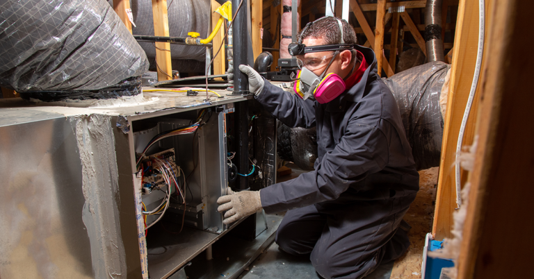 trained professional inspecting and replacing a central heating system